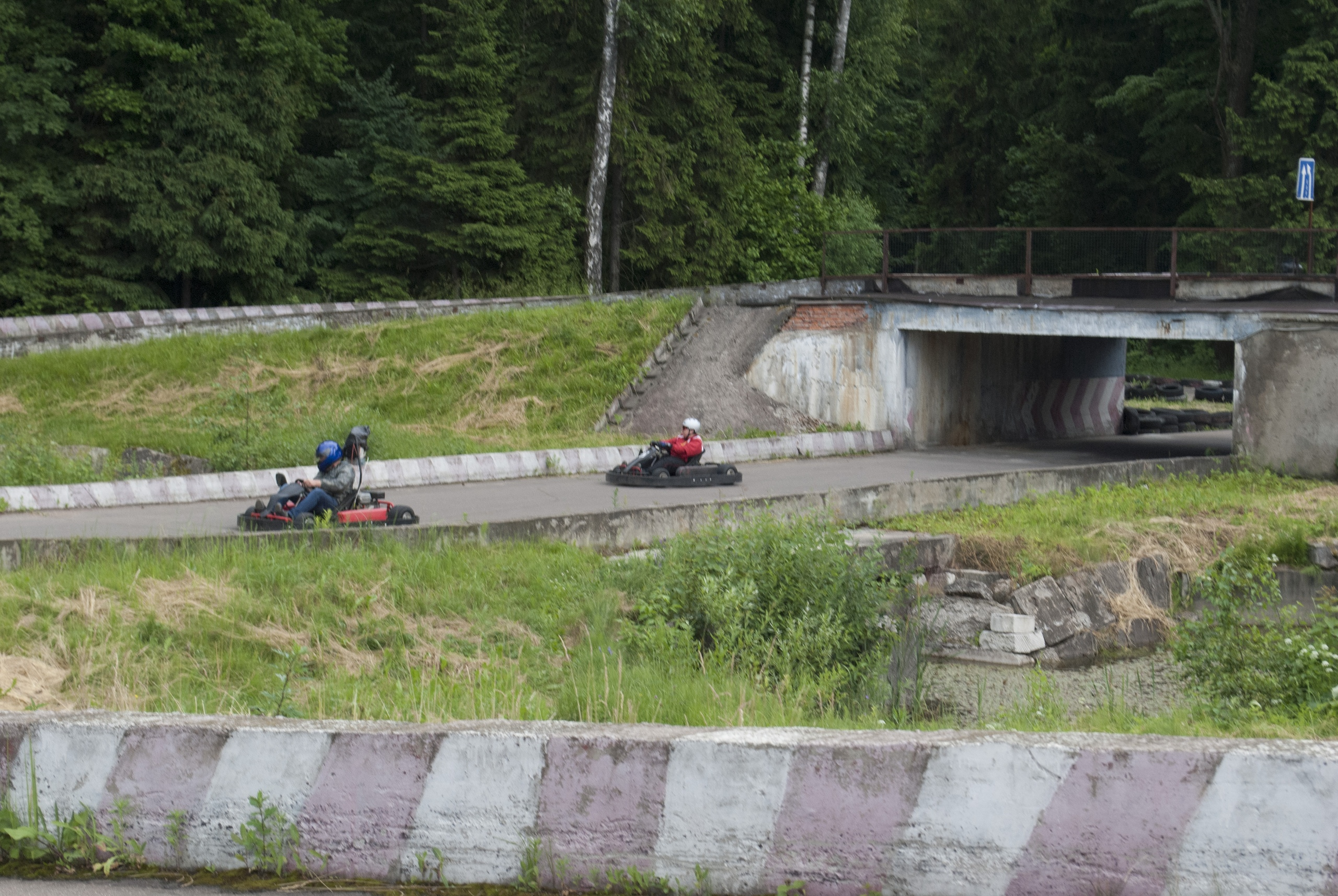 Павел Дрёмин и Андрей Заяц. В процессе езды по треку, вылетают из последнего туннеля на треке. Вид сбоку.