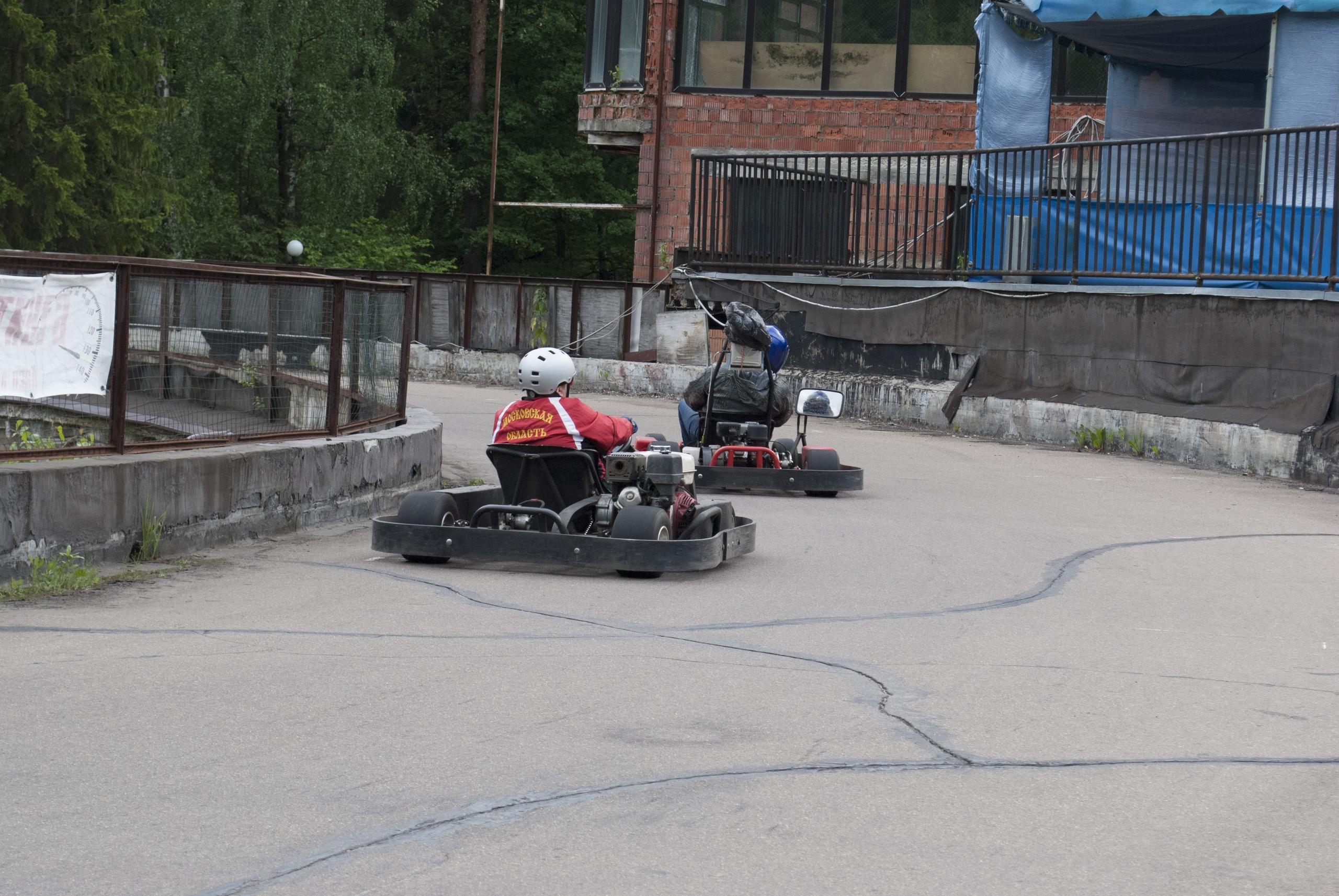 Павел Дрёмин и Андрей Заяц, в процессе езды по треку. Пролетают участок трассы с бетонным ограждением, перед спуском. Вид сзади.