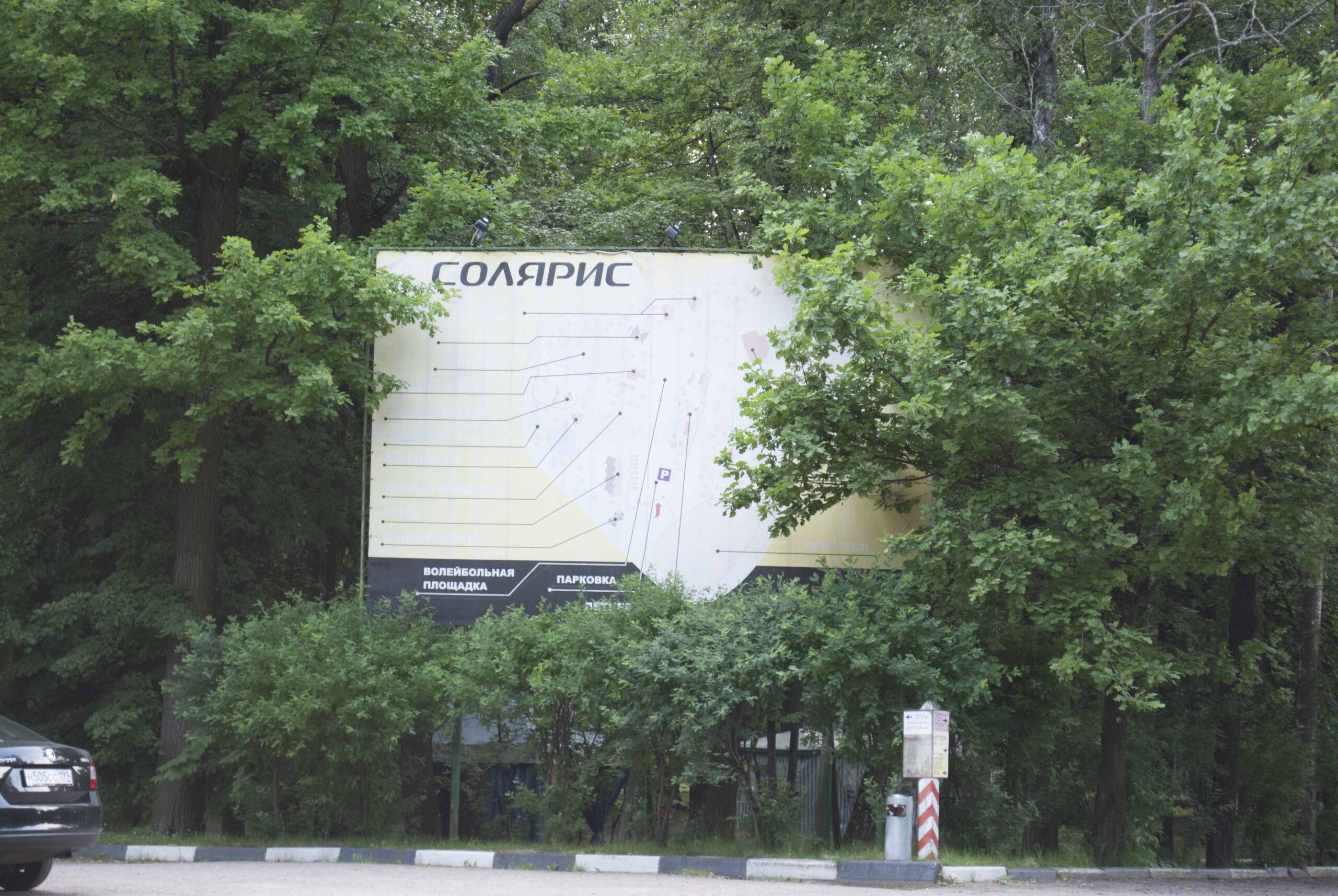 на фоне деревьев, почти утопая в них, стоит потрёпаный временем рекламный щит с надписью Солярис и картой зданий загородного клуба